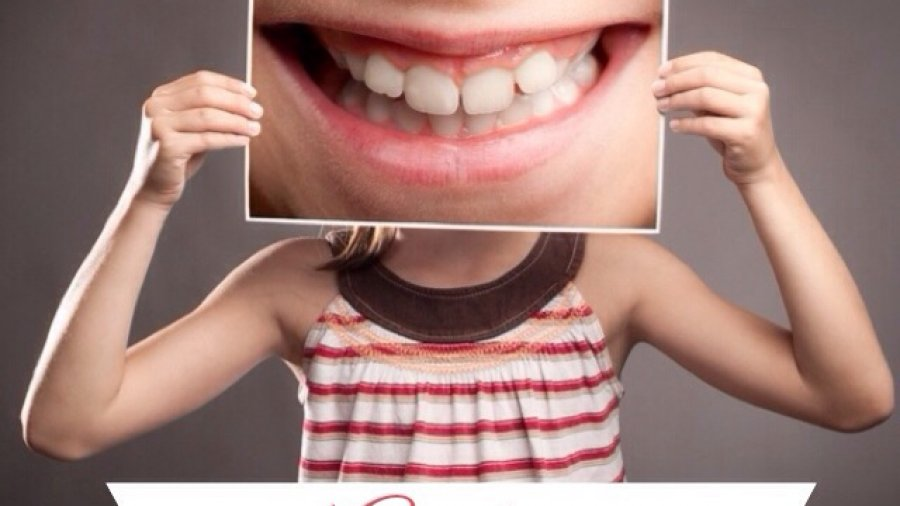 Picture of a girl holding a photo of teeth for National Oral Health Month post