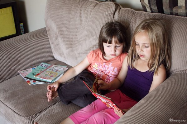 Reading to her little sister and getting her hours in for the TD Summer Reading Club.