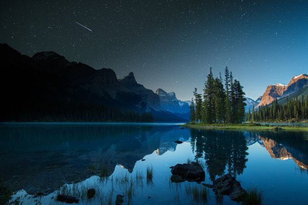 A shooting star goes over Spirit Island on Maligne Lake in Jasper, Alberta, Canada. Photo credit Ryan Bray, Parks Canada
